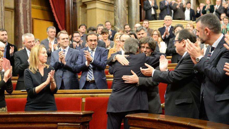 Artur Mas y Carles Puigdemont se abrazan antes del inicio del debate de investidura. / SANDRA LÁZARO
