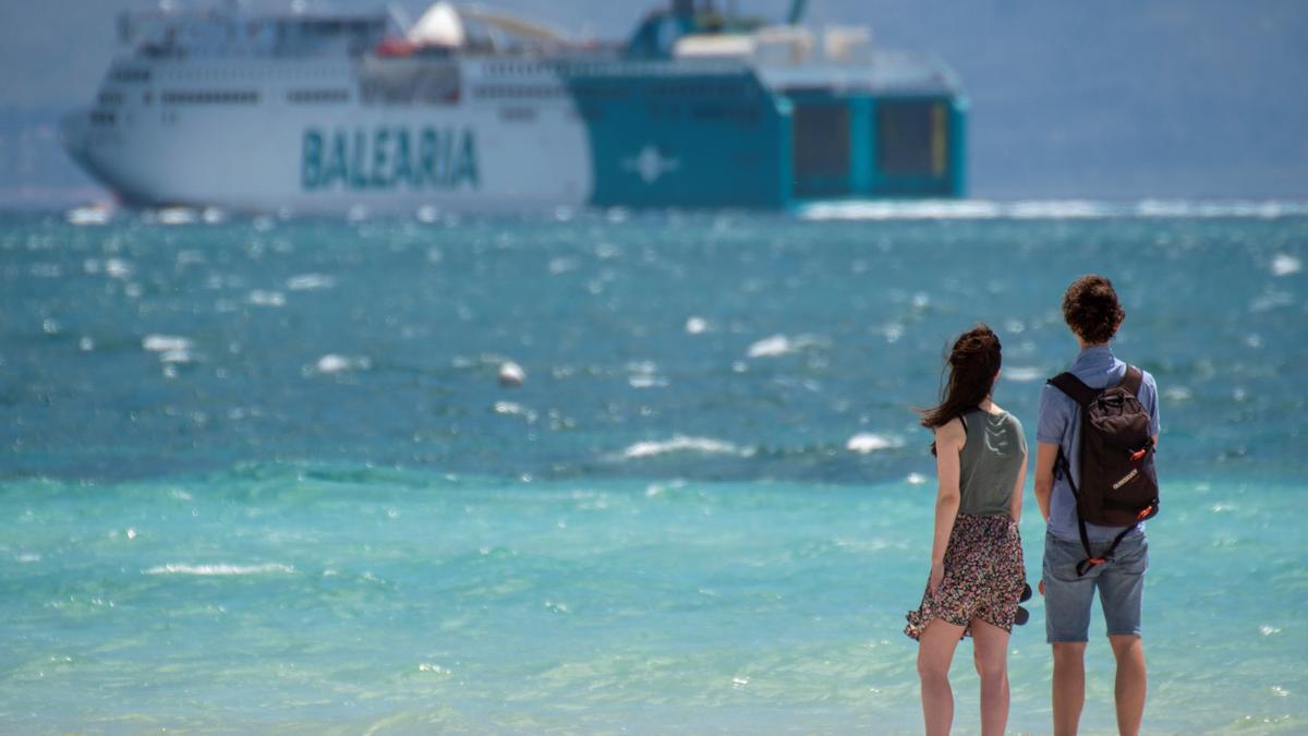Jóvenes en Mallorca delante de un ferry