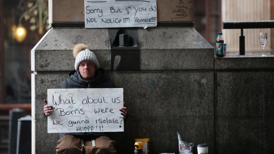 Una persona sin hogar sostiene un cartel sobre el confinamiento en Londres © REUTERS/Hannah McKay