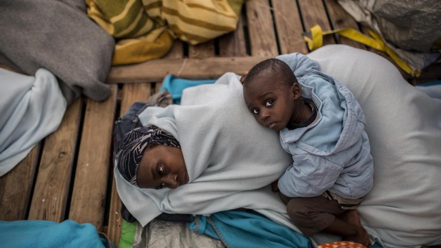 Fanta Diaby y su hijo Moustafa Diaby, de 1 año y 11 meses, procedentes de Costa de Marfil, se protegen del frío con una manta en la cubierta del barco Open Arms / Olmo Calvo