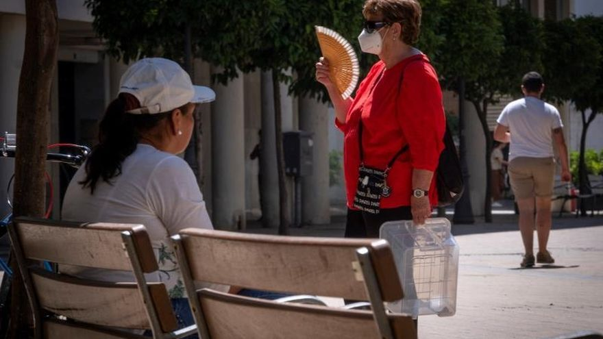 - Una mujer con mascarilla y abanico camina por una céntrica calle de Huelva..