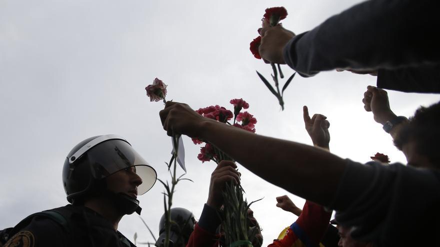 Manifestantes entregan claveles a un agente de la Guardia Civil