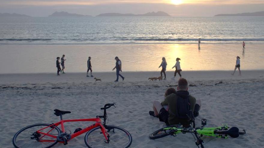 Varias personas pasean por la playa de Samil, en Vigo.