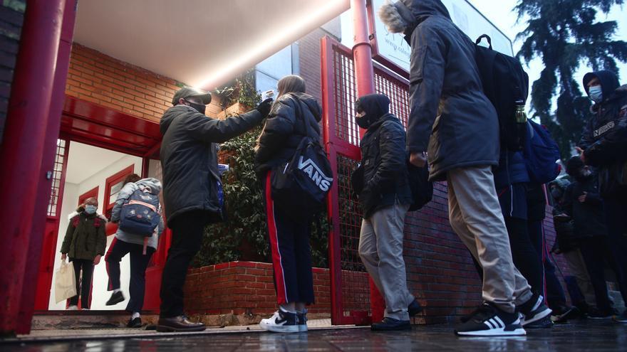 Un trabajador toma la temperatura a un alumno antes de entrar a un colegio.