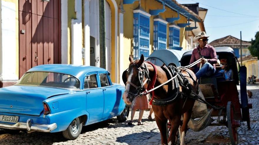 Fotografía del 17 de enero de 2020 que muestra un coche tirado a caballo pasando junto a un automóvil clásico, por una de las calles de Trinidad, en Sancti Spíritus (Cuba). El intensificado embargo de EE.UU. y la quiebra del turoperador Thomas Cook han puesto en jaque a Cuba, que perdió casi 500.000 turistas en 2019. Para revertir la situación, los hoteleros apuntan a China, Rusia y sobre todo a los cada vez más cubanos que se pueden permitir unas buenas vacaciones.