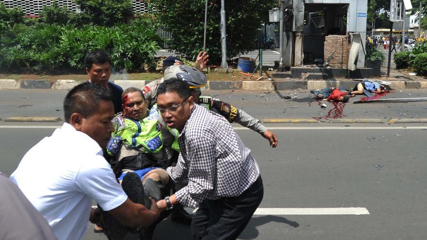 Varias personas trasladan a un policía herido cerca del lugar en el que se ha producido la explosión en Yakarta