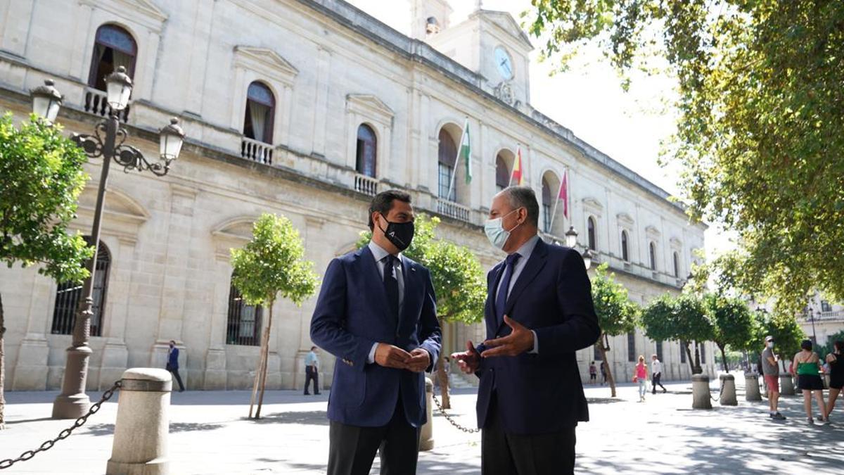 El presidente andaluz, Juan Manuel Moreno, con el alcalde de Tomares, José Luis Sanz, ante el Ayuntamiento de Sevilla.