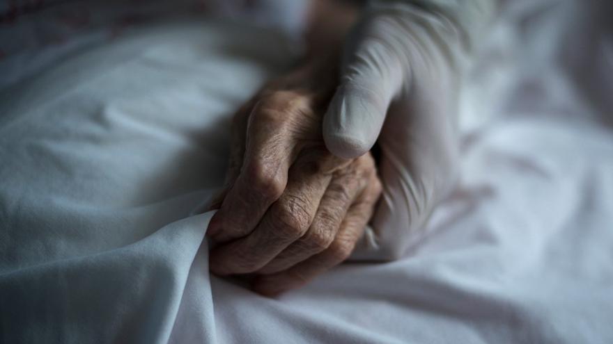 Una trabajadora de la residencia de mayores San Carlos de Celanova sujeta la mano de una residente.