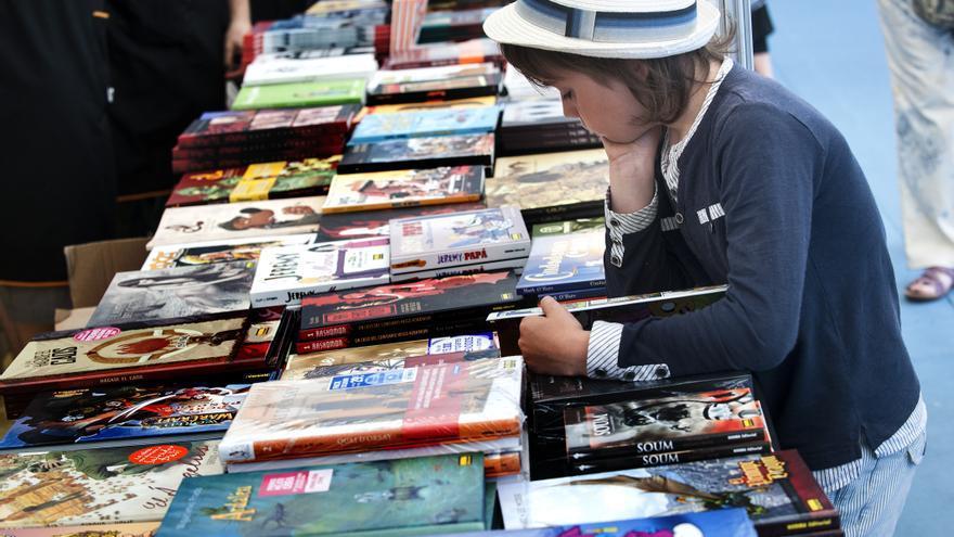Un niña consulta un stand en la Feria del Libro de Santander. |