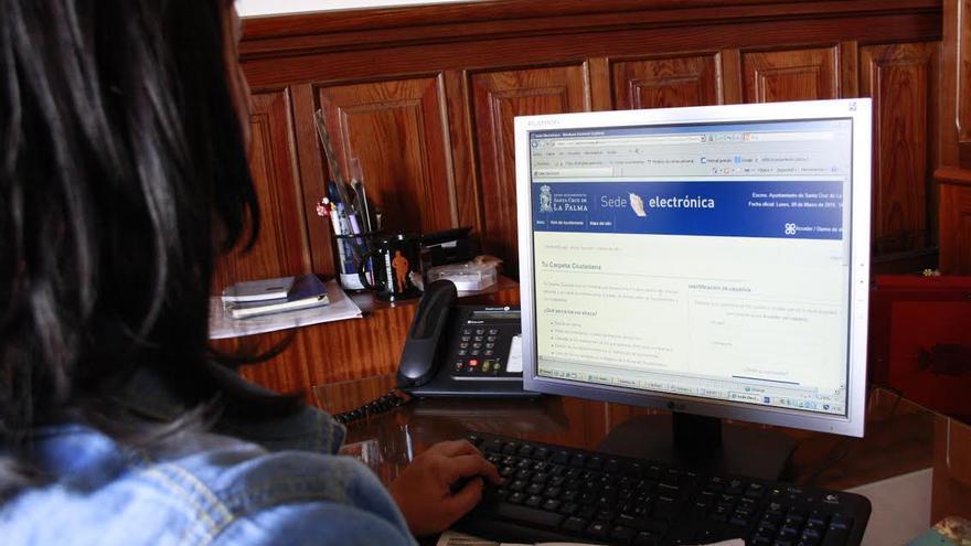 En la imagen, una persona accede desde una ordenador a la 'Sede Electrónica' desde donde  puede realizar sus pagos, comprobar el estado de sus recibos, obtener copia de los mismos.