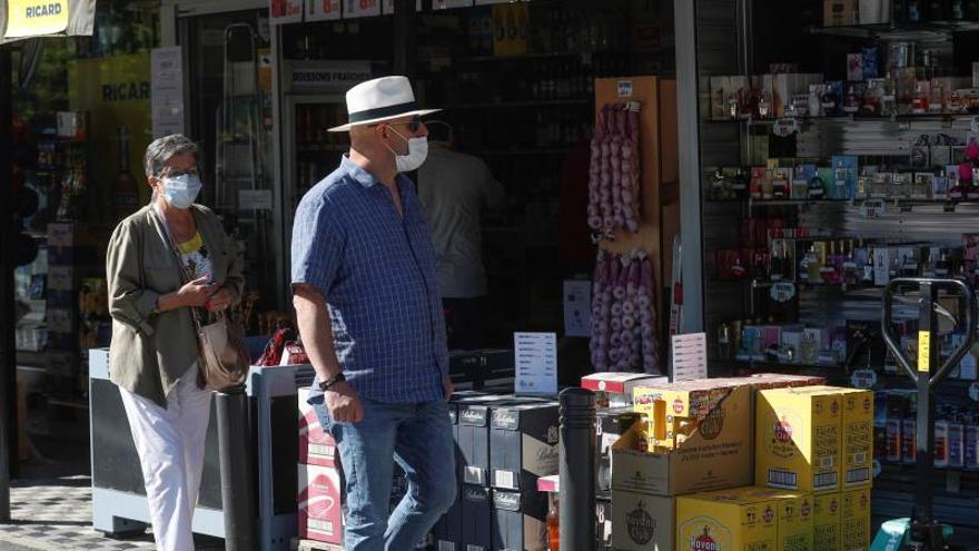 Varias personas pasan junto a un establecimiento de alcohol en los numerosos comercios establecidos en la frontera en la localidad de Irún este domingo.