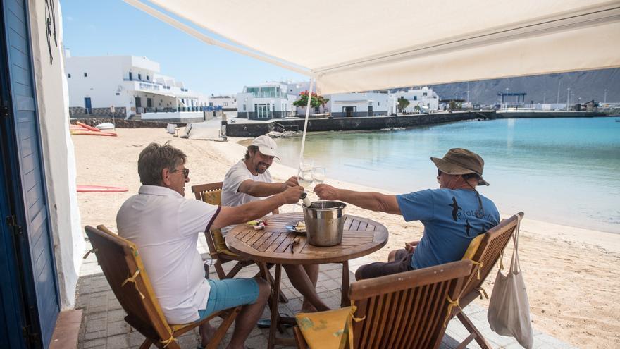 Tres personas brindan en La Graciosa, en fase 3 de la desescalada.