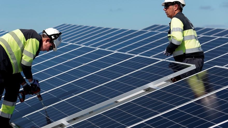 Dos operarios fijan paneles solares en la instalación.