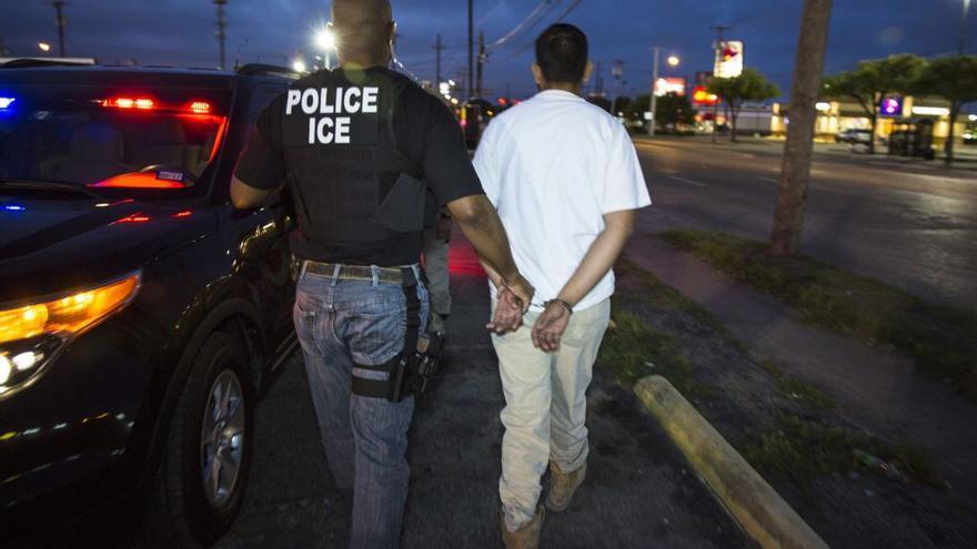 Un agente del ICE se lleva esposado a un detenido en una redada contra sin papeles.