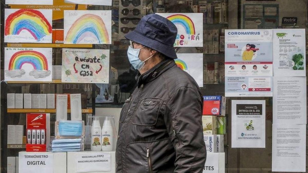 Un señor pasea con mascarilla frente a un comercio del centro de Santander.