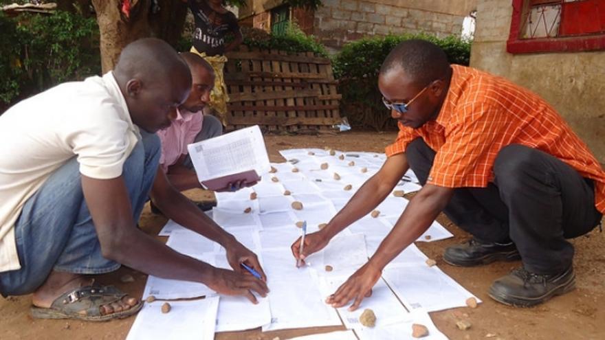 La gente local añade calles o nombres de edificios, sobre papel, al mapa que luego se digitalizará. Esto es en Congo.