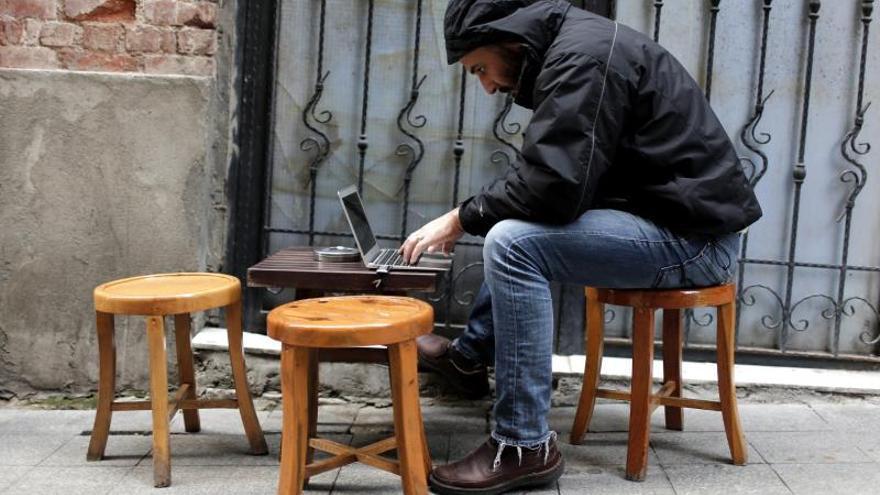 Un hombre navega por Internet en su ordenador portátil.