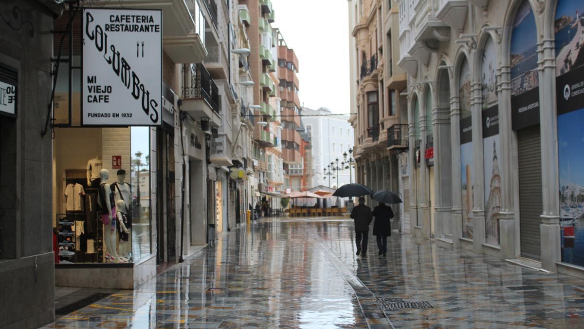 Dos personas pasean bajo la lluvia por la calle Mayor de Cartagena