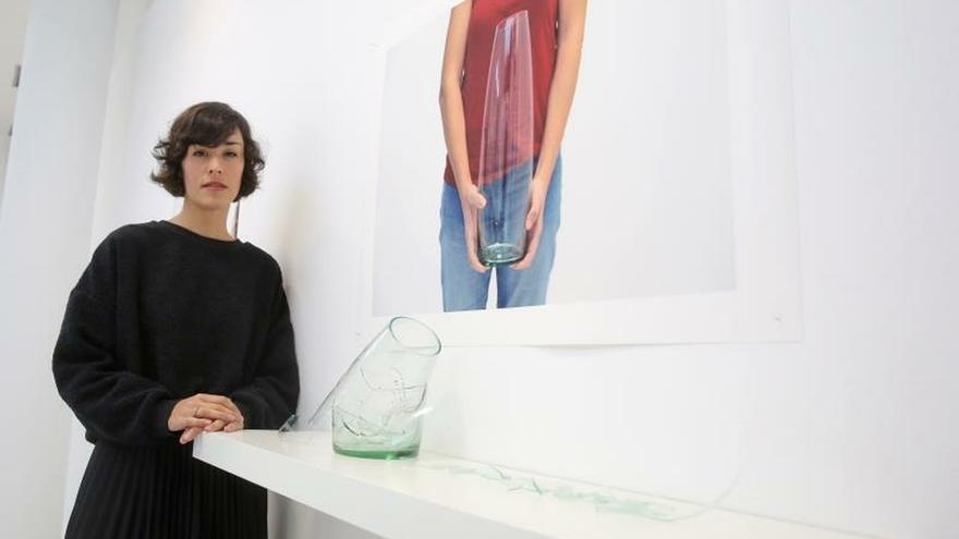 """La artista Gema Rupérez posa junto a uno de los nueve jarrones expuestos en la Casa de la Mujer de Zaragoza que guardan una historia de violencia machista, la de una superviviente que ha destruido y reconstruido su propio """"testigo emocional"""" y que forma ahora parte de la muestra 'Las formas de olvido'."""