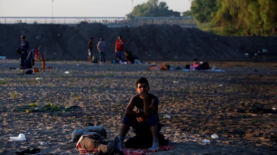 Decenas de personas hondureñas descansan este martes, a las orillas del río Suchíate tras que la Guardia Nacional de México impidiera a migrantes cruzar, en Tecún Umán (Guatemala). Cientos de migrantes cruzaron ayer el río Suchiate, que separa Guatemala de México, a fin de entrar en territorio mexicano ilegalmente luego de que el Gobierno rechazara su solicitud formal para ingresar al país.