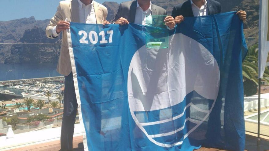 Borja Pérez (i), David Pérez y Jonathan Felipe muestran la Bandera Azul.