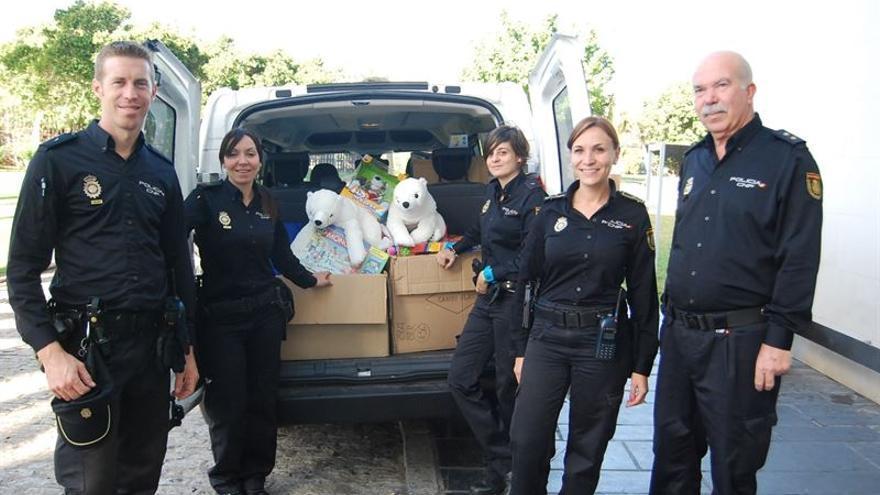 Los agentes y el comisario posan junto a los regalos para los menores ingresados
