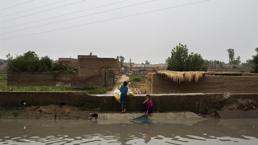 Dos jóvenes refugiadas afganas lavan ropa en un riachuelo el pasado 4 de julio, en el campo de Kababian, en el noroeste de Pakistán | FOTO: EFE