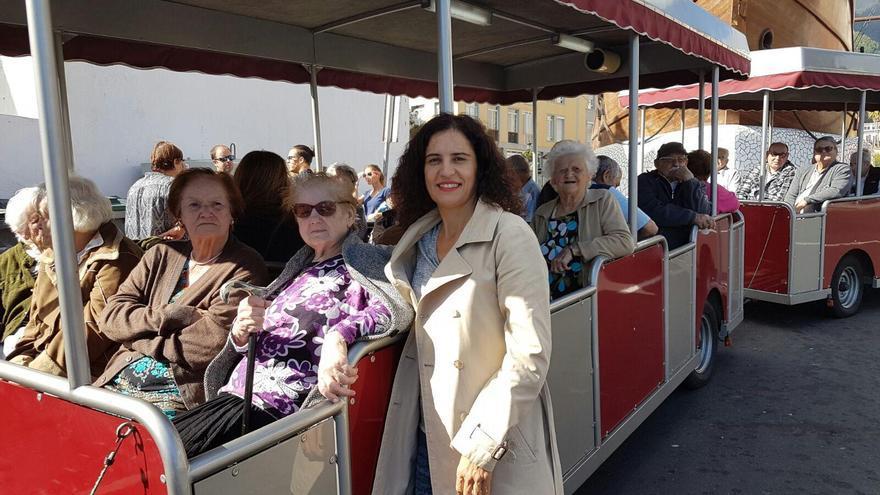 La consejera de  Asuntos Sociales del Cabildo de La Palma, Jovita Monterrey, junto al tren turístico, con un grupo de mayores.