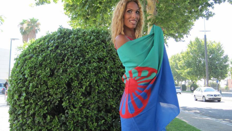 Jennifer posa envuelta en la bandera romaní en su barrio de Córdoba.
