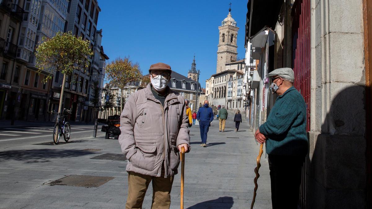 Dos mayores conversan en una calle de Vitoria.