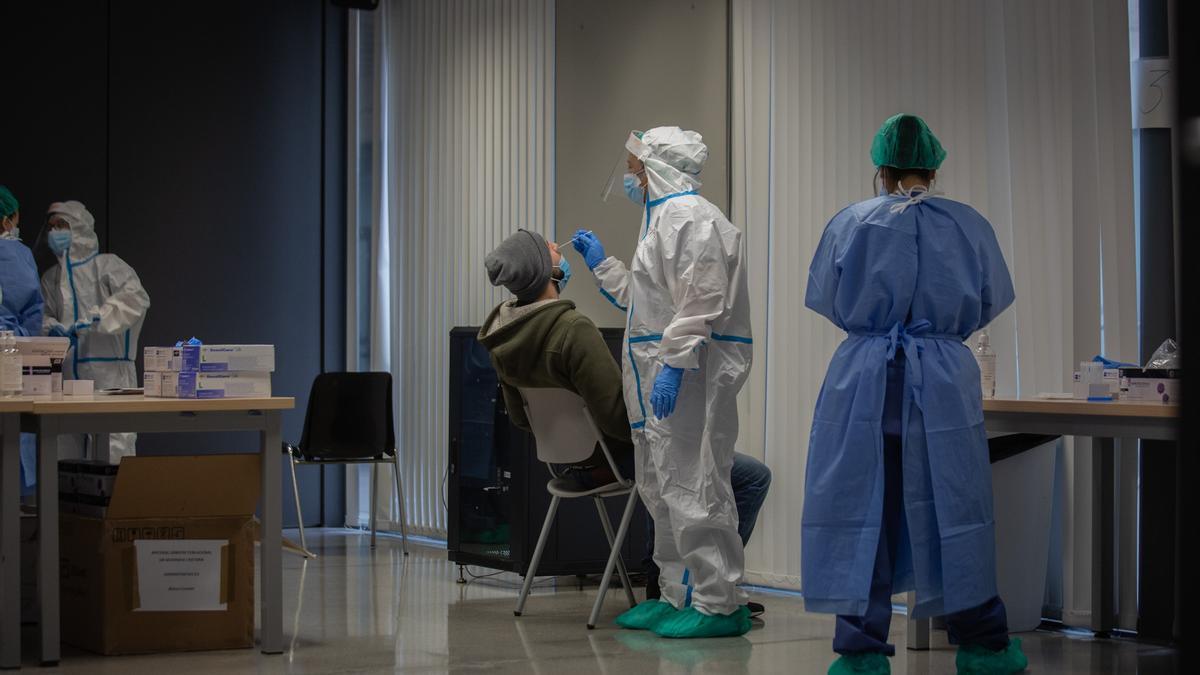 Archivo - Un hombre se realiza una prueba PCR en un dispositivo de cribados masivos