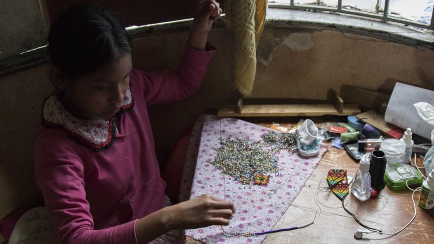 Las niñas y las mujeres son las encargadas de fabricar las artesanías que luego venderán en la calle, el principal sustento para la familia