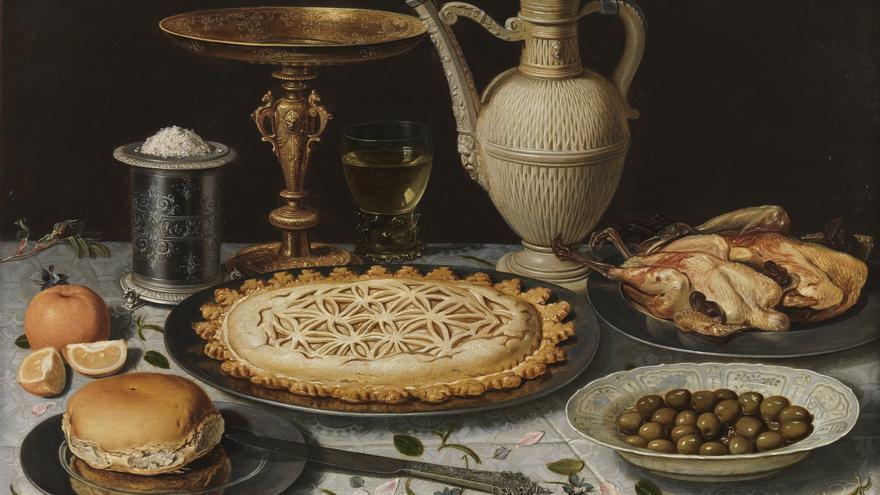 Mesa con mantel, salero, taza dorada, pastel, jarra, plato de porcelana con aceitunas y aves asadas