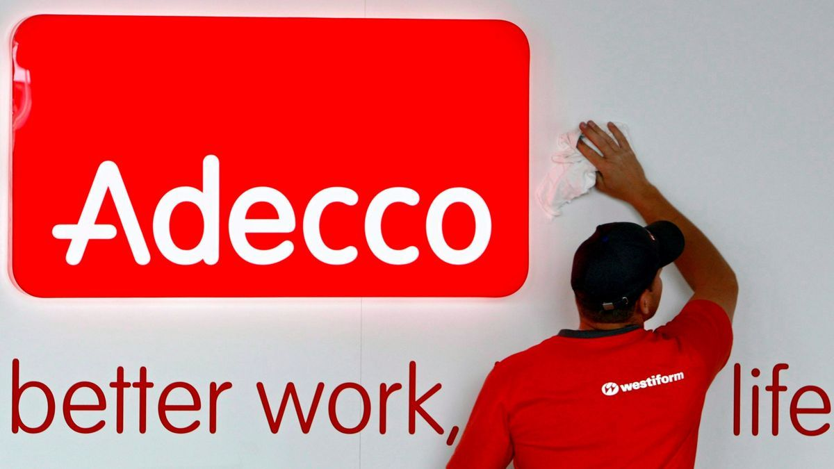 Un operario limpiando un cartel con el logotipo de la compañía de trabajo temporal Adecco. EFE/Laurent Gillieron/Archivo