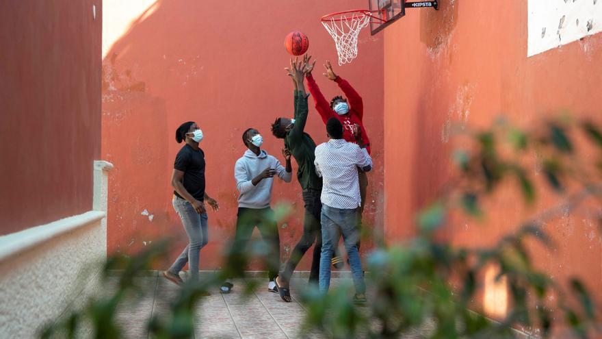 Menores migrantes no acompañados, llegados en patera a Gran Canaria en 2020, juegan al baloncesto en el centro especializado en adolescentes de Tenerife.