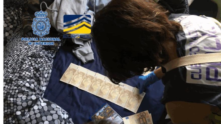 Una agente de la Policía Nacional cuenta el dinero falso incautado en la operación.