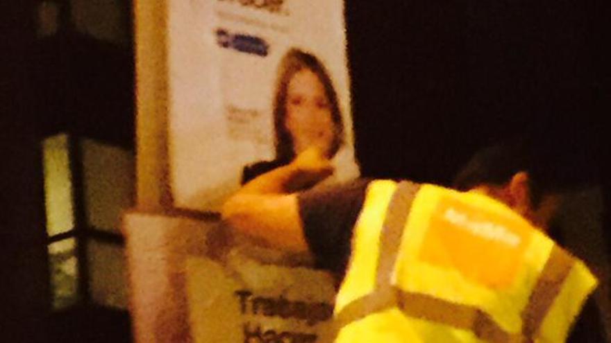 Un operario tapando un cartel de Nueva Canarias con uno del PP.