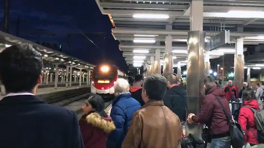 Usuarios esperan un tren de Cercanía de la línea C-2 en la estación del Norte de Valencia que ha llegaba con 20 minutos de retraso.