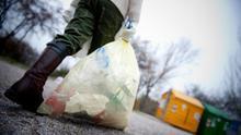 Un niño, a punto de reciclar una bolsa llena de briks y envases de plástico.