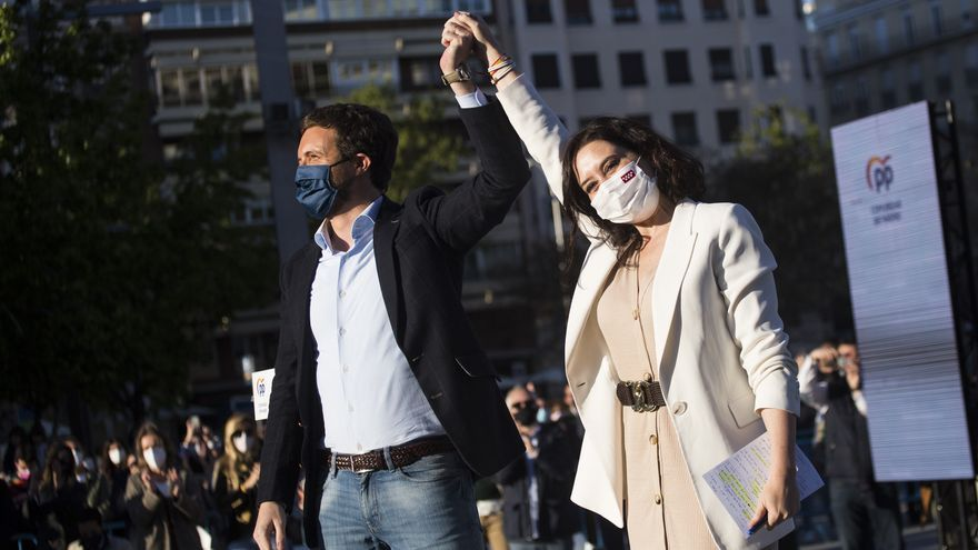 El presidente del PP, Pablo Casado, y la candidata a la reelección en las eleciones madrileñas, Isabel Díaz Ayuso, durante el acto de pegada de carteles del partido de cara a las elecciones madrileñas, a 17 de abril de 2021, en Madrid (España).