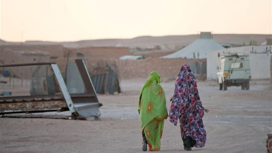 Dos mujeres caminan por el campamento ataviadas con las melfas, una de las señas de identidad del pueblo saharaui.   ALOUDA