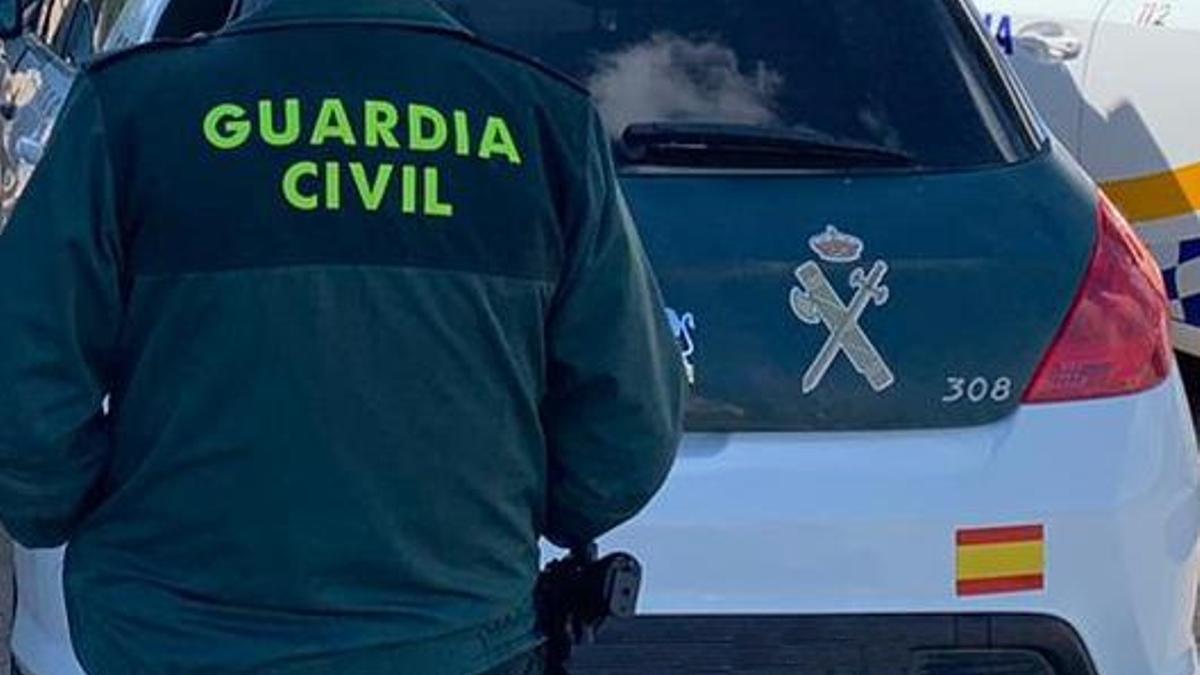 Un agente de la Guardia Civil de espaldas y junto a un vehículo oficial del cuerpo.