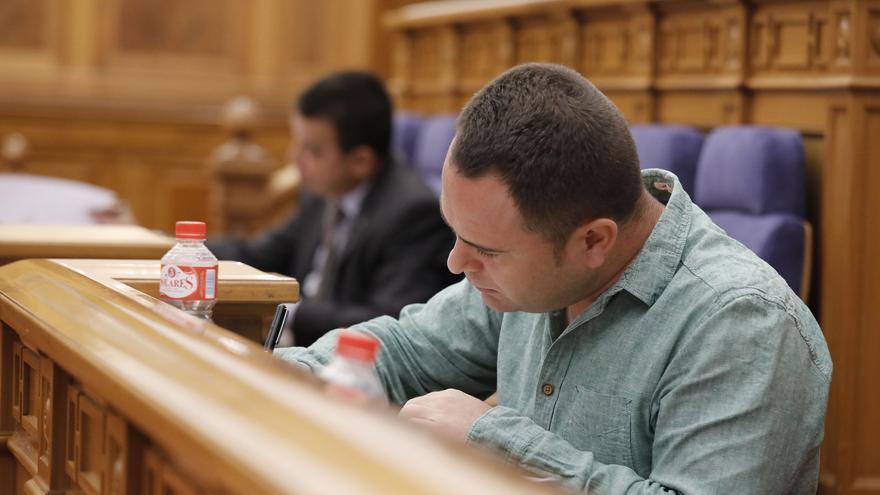 El diputado de Podemos, David Llorente, en primer plano y al fondo del consejero de Medioambiente durante el Pleno