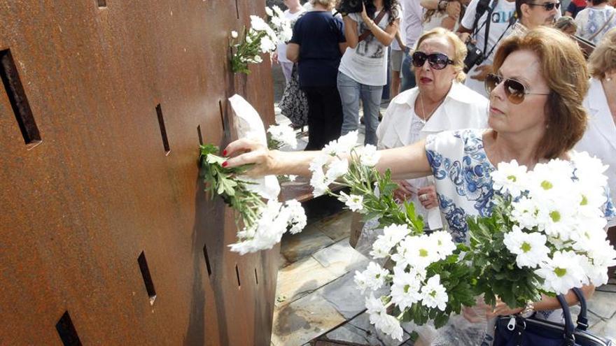 """Una mujer pone flores en el monumento """"Luces en el Vacío"""" de la playa de Las Canteras, en Las Palmas de Gran Canaria, durante el acto de homenaje a las 154 víctimas del vuelo de Spanair JK5022 celebrado hoy cuando se cumplen cinco años del accidente. EFE/Elvira Urquijo A."""