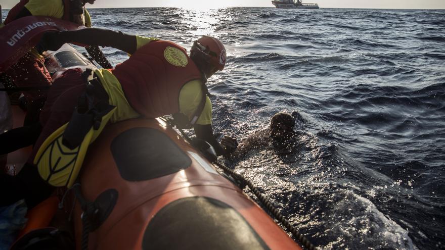 La tripulación del Open Arms saca del agua a uno de los ocupantes de una lancha que se negaban a ser trasladados a Túnez, que se hizo cargo de su rescate este domingo.