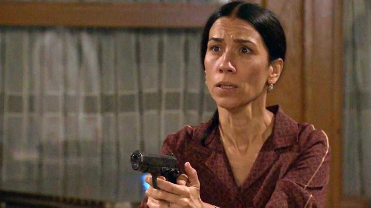 Manolita apunta a Beltrán con la pistola