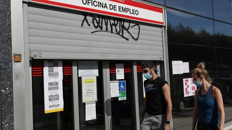 Dos jóvenes pasan ante una oficina de empleo en Madrid.