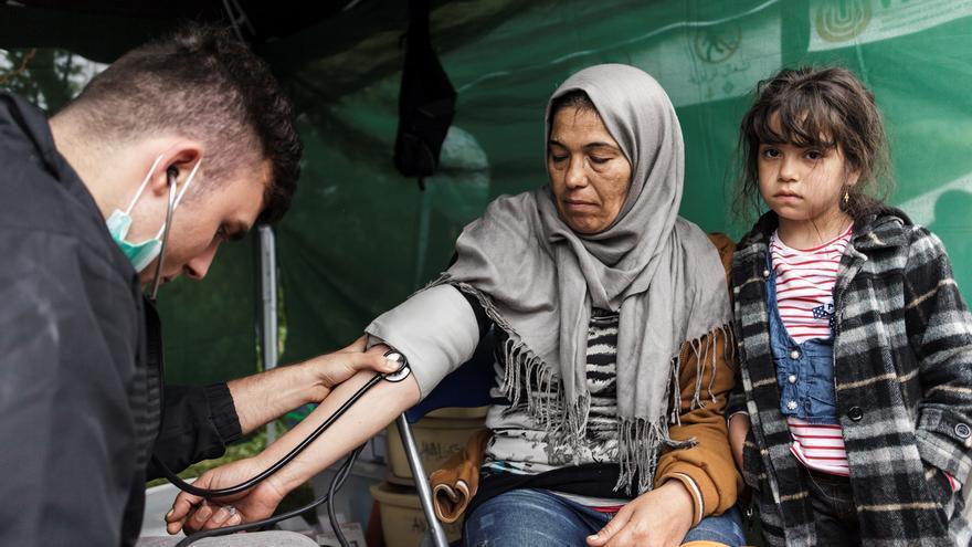 Bara, 7 años, espera mientras Momvilo Djurdjevic, doctor de MSF, toma el pulso a su tía. Proceden de Irak y tratan de llegar a Alemania, donde residen otros miembros de su familia. Muchos refugiados presentan tos,  gripe, afecciones gastrointestinales y enfermedades cutáneas, que a menudo se dan como resultado de las condiciones a las que se enfrentan durante el viaje. Los equipos también asisten a enfermos crónicos con diabetes o asma o con problemas cardíacos que no han sido atendidos de manera adecuada y que se han deteriorado en el transcurso del viaje. Fotografía: Achilleas Zavallis