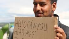 Refugiado mostrando un cartel que versa sobre la situación en Siria