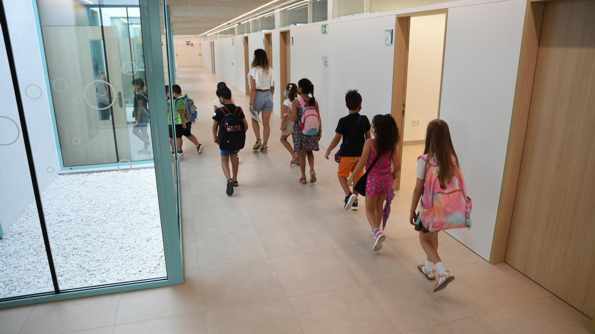 Una profesora acompaña a alumnos de Educación Primaria a un aula. La educación es uno de los sectores que más empleo genera en septiembre.